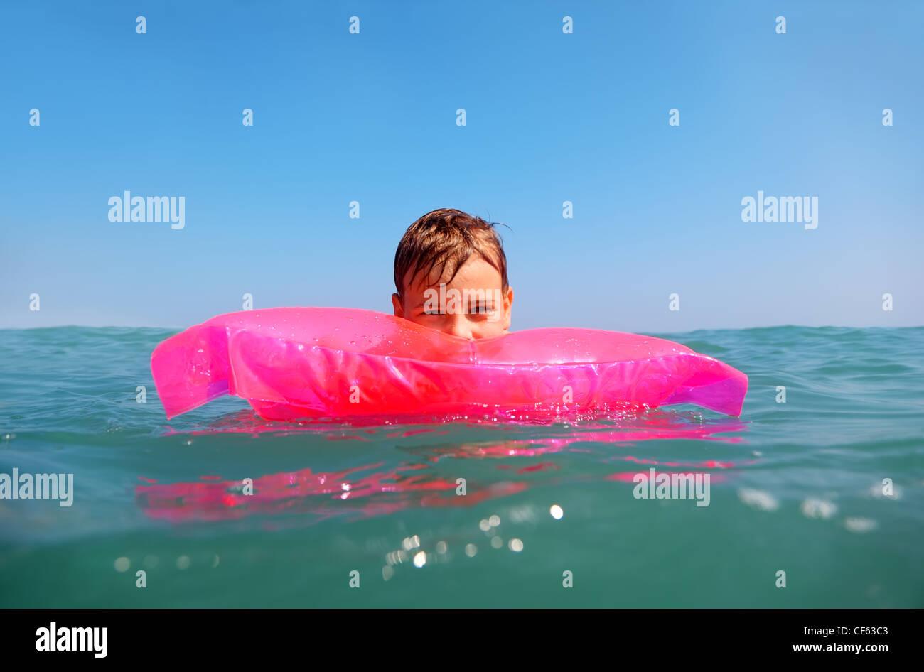 Der kleine Junge schwimmend im Meer auf aufblasbare rosa Matrese. erschossen von Unterwasser-Box, Wasser auf dem Stockbild