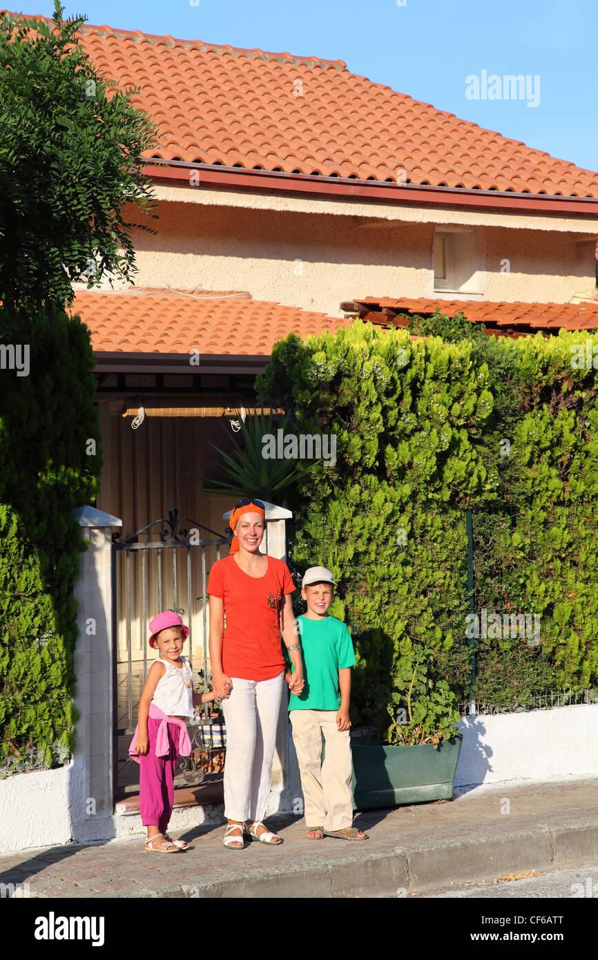 Mutter mit zwei Kindern steht tagsüber in der Nähe aufgenommen am Resort im Haus Stockbild