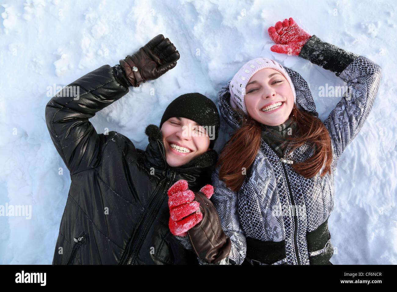 Zwei liebenden Menschen Lügen auf im Winter auf Schnee halten Hände und Lächeln Stockbild