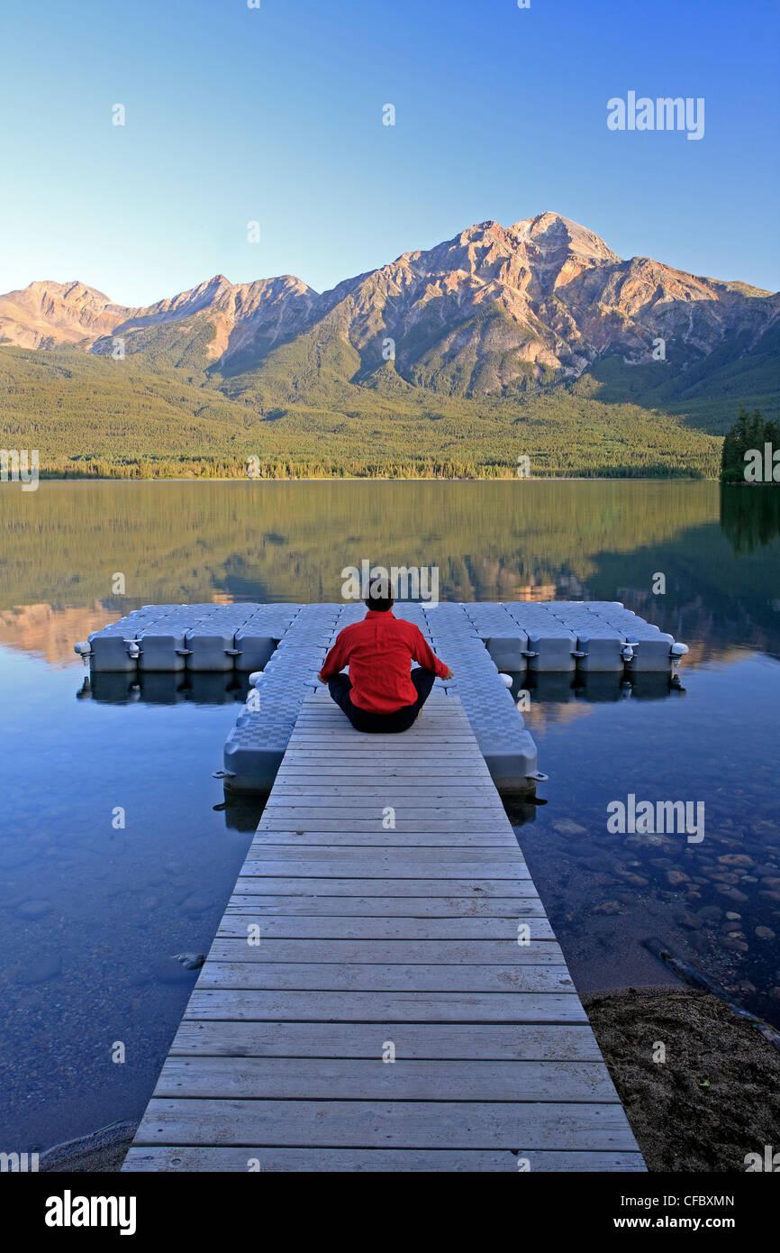 Mittleren Alters männlichen meditieren auf dock am Pyramid Lake, Jasper Nationalpark, Alberta, Kanada. Stockfoto