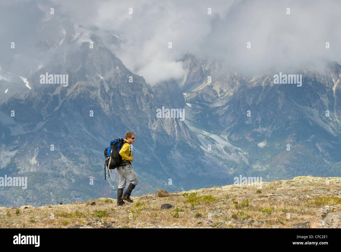 Ein Wanderer durchquert einen Grat im Bereich Kartoffel mit einem nebligen Blick des Bereichs Niut hinter, British Stockbild