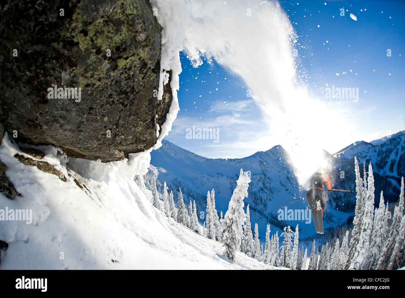 Ein männlicher Skifahrer voller Testosteron startet aus einen Sprung an Wildwasser Wintersportort, Nelson, Stockbild