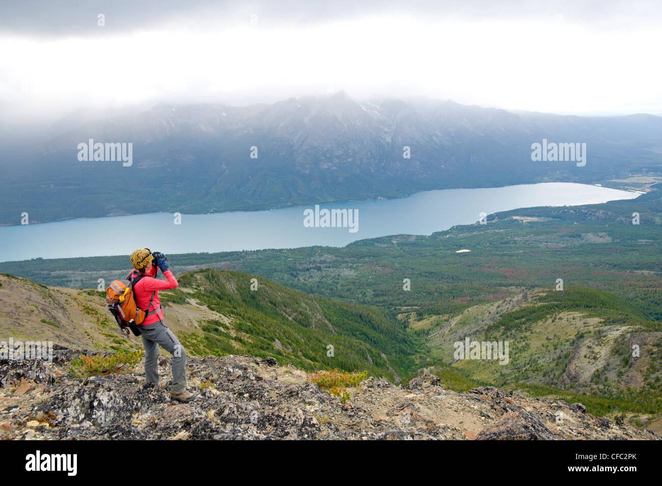 Eine Frau Umfragen über Tatla Lake mit dem Fernglas, British Columbia Coast Mountains Stockbild