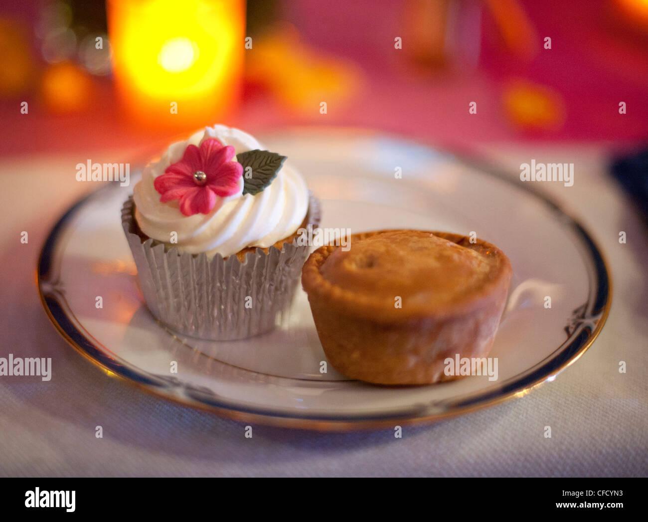 Eine Tasse Kuchen und Torte sitzen auf einem Teller, beleuchtet von einer Kerze mit flachen Fokus bei einer Hochzeit Stockbild