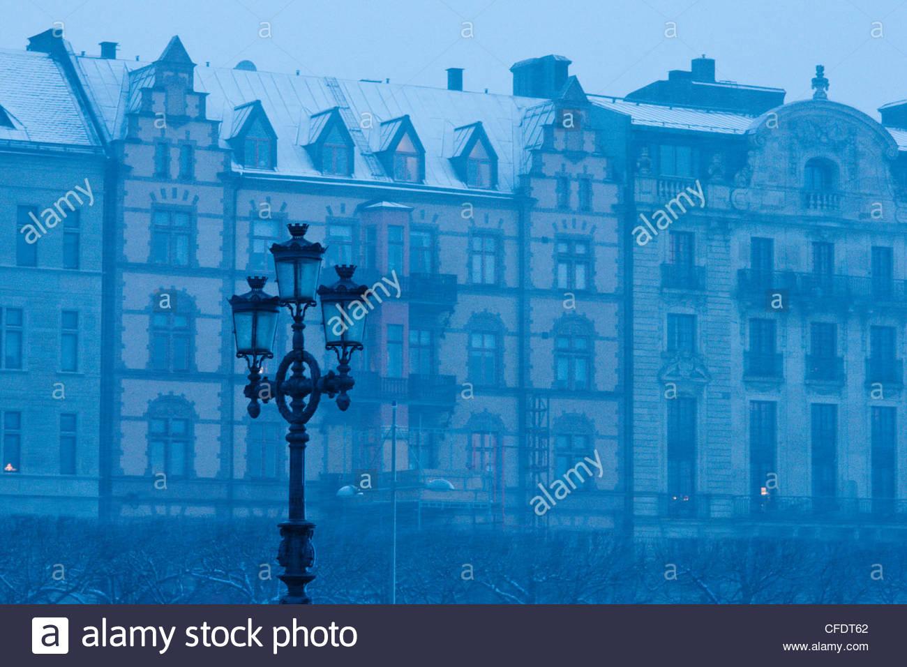 Lampost im Vordergrund der historischen Gebäuden genommen während, Schneefälle, Djurgarden, Stockholm, Stockbild