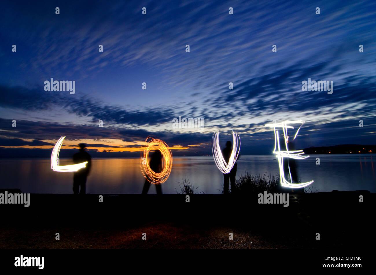 Familie verwendet Taschenlampen malen Wort Liebe entlang Stockbild