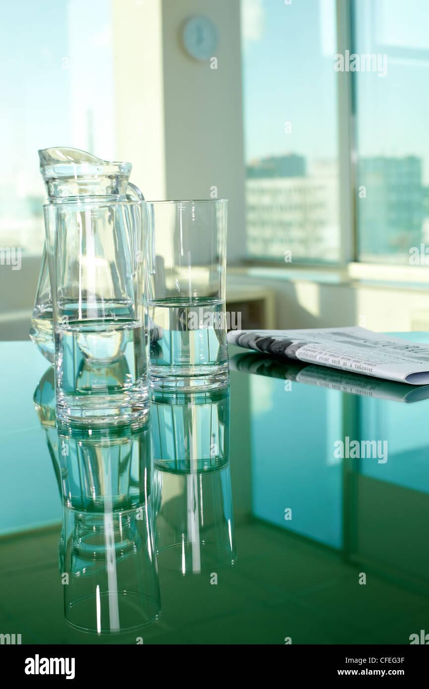 Arbeitsplatz mit Glaswaren und Zeitung Stockbild