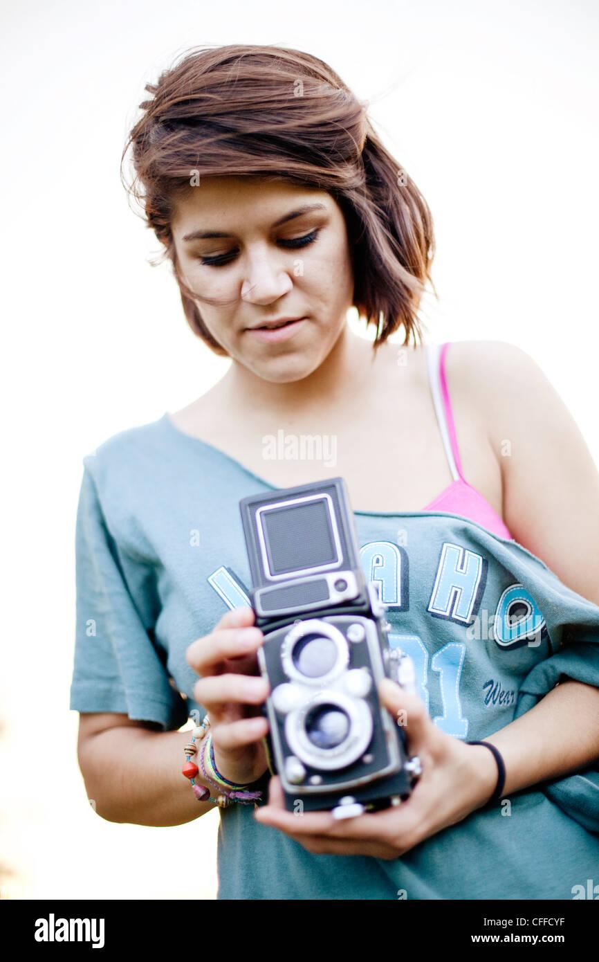 Eine junge Frau nimmt ein Foto mit einer klassischen Kamera. Stockbild