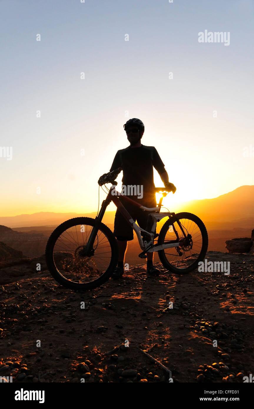 Eine Silhouette eines Mountain-Bikers bei Sonnenuntergang am Stachelbeere Mesa im südlichen Utah. Stockbild