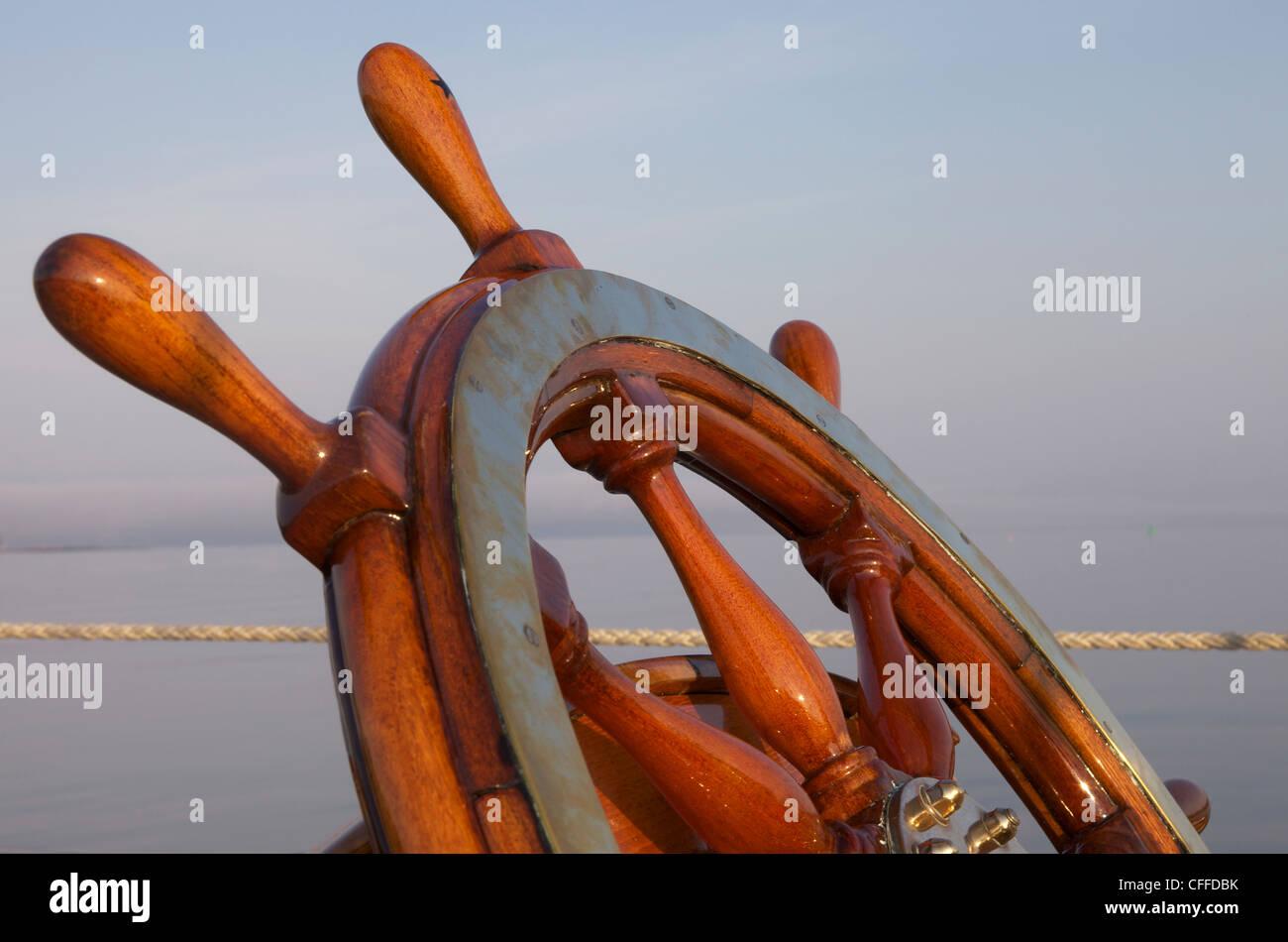 Ein warmes Glühen unterstreicht das Steuerrad an Bord einer klassischen Segelyacht als Sonnenuntergang Ansätze. Stockbild