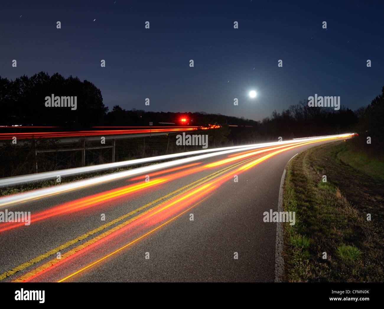 helle Streifen vom Verkehr auf der Straße in der Nacht Stockbild
