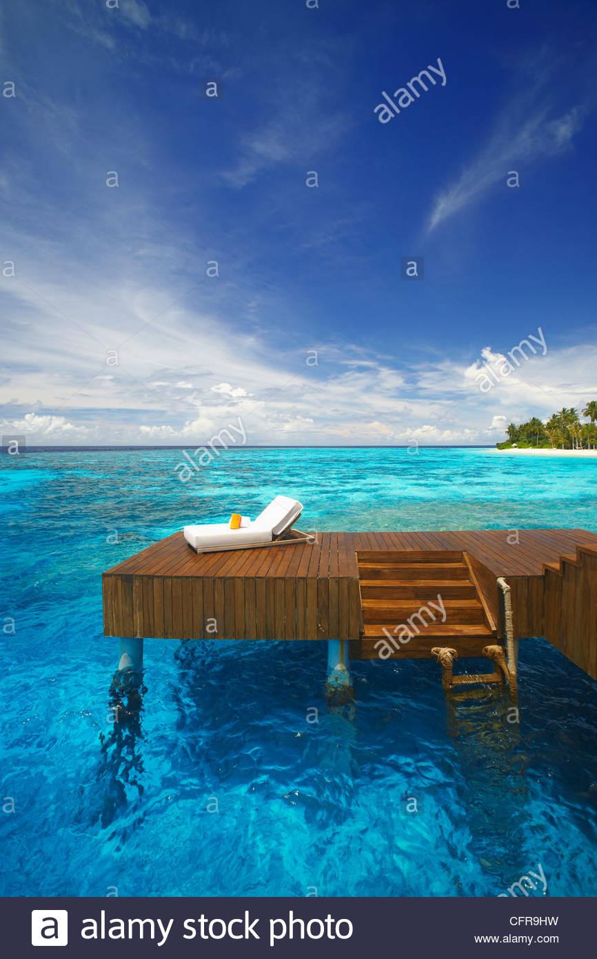 Sonnenliege und Steg in der blauen Lagune auf der tropischen Insel, Malediven, Indischer Ozean, Asien Stockfoto