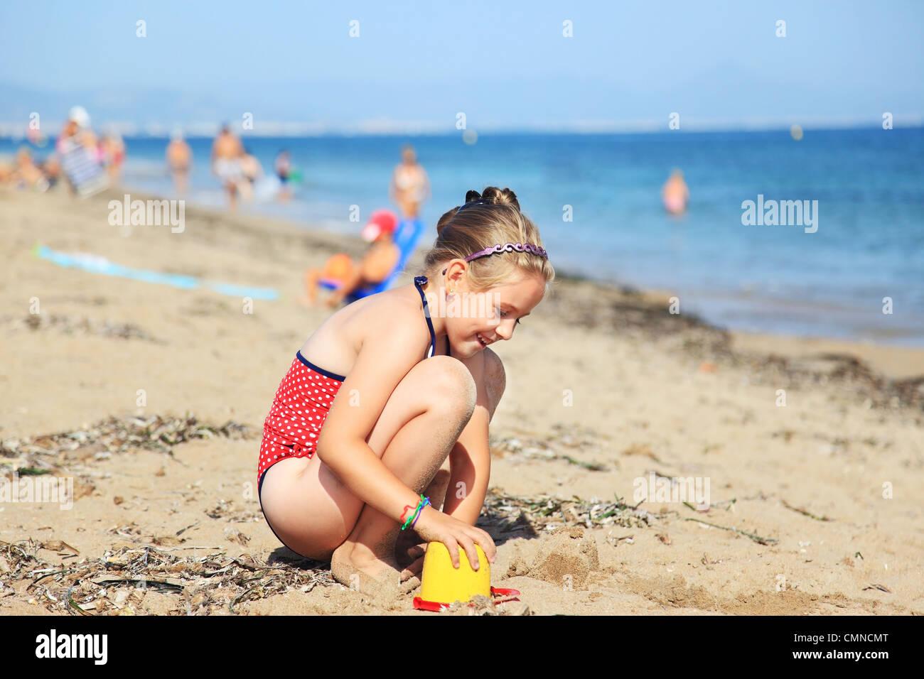 Kinder spielen mit Kunststoff-Spielzeug am Strand Stockbild