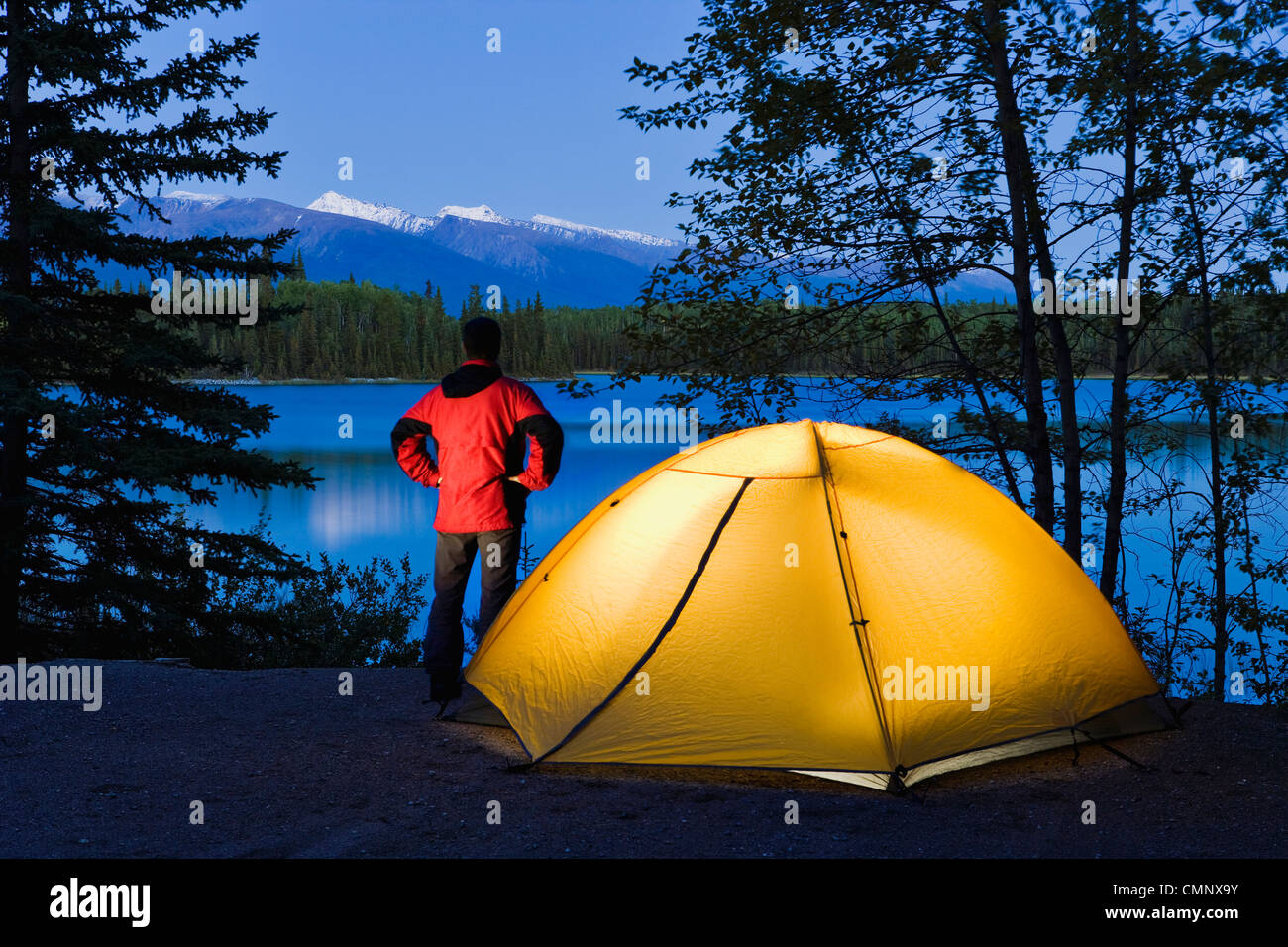 Wanderer durch ein Zelt mit Blick auf Boya Lake bei Dämmerung, Boya Lake Provincial Park, Norden von British Stockbild