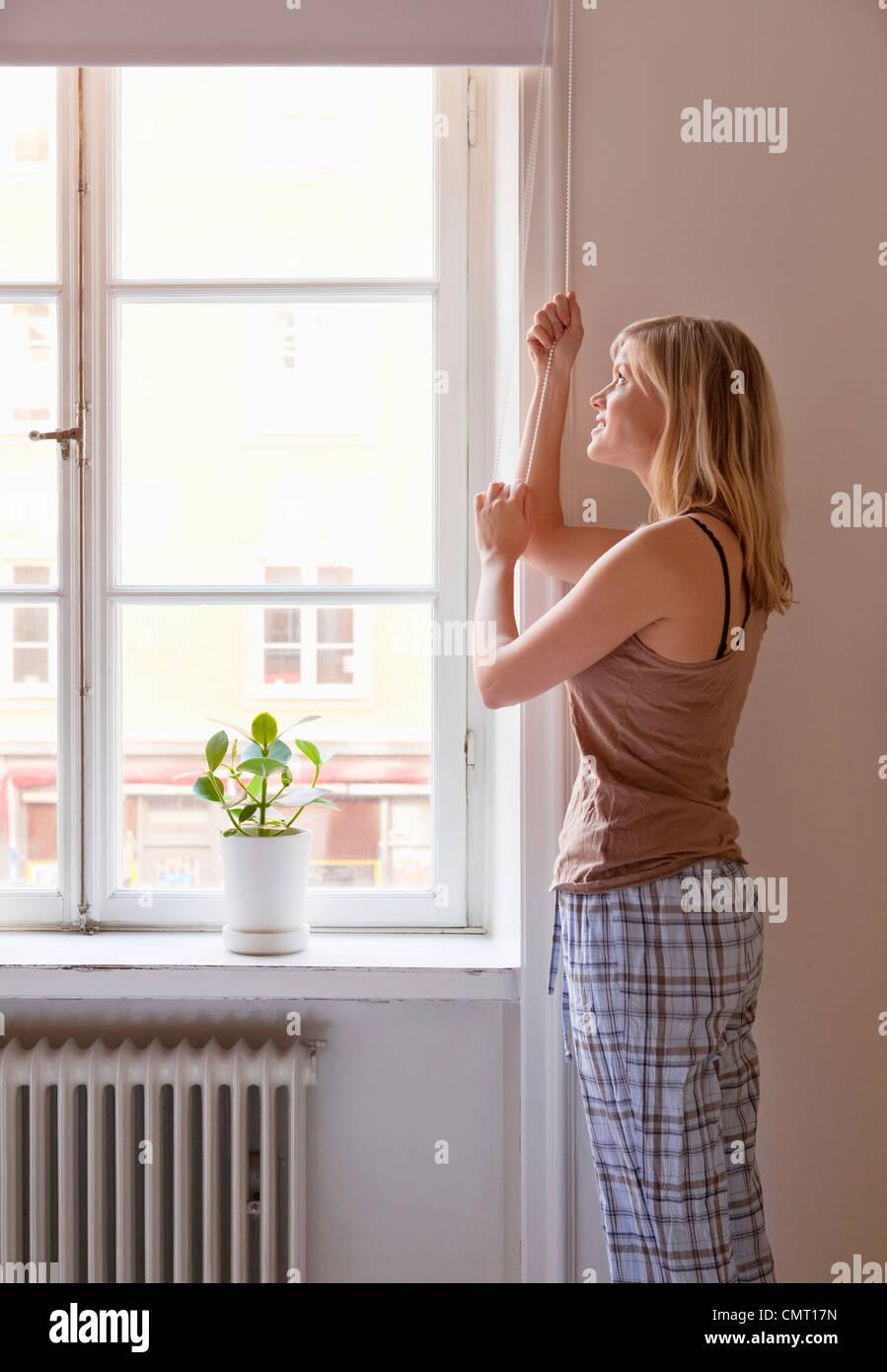 Frau zu öffnendes Fenster blind Stockbild