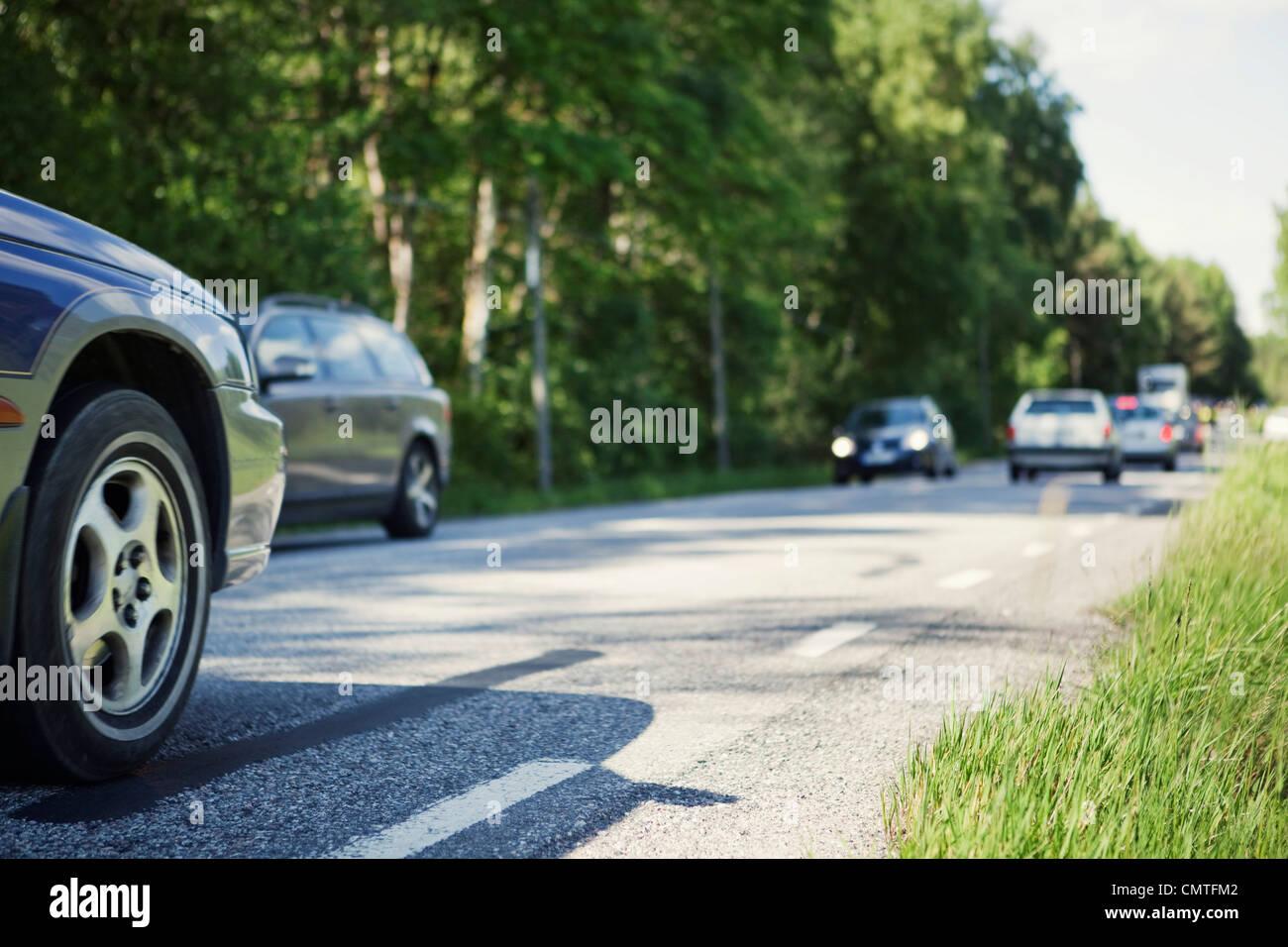 Autos auf der Landstraße durch Bäumen gesäumt Stockbild