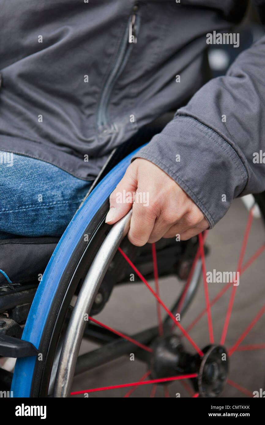 Die Hand des Mannes auf Rollstuhl-Rad Stockbild