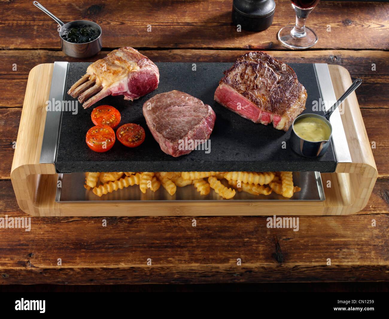 Rack mit Lamm-Rib-Eye und Filetsteak auf einem heißen Lavastein mit Chips unter Stockbild