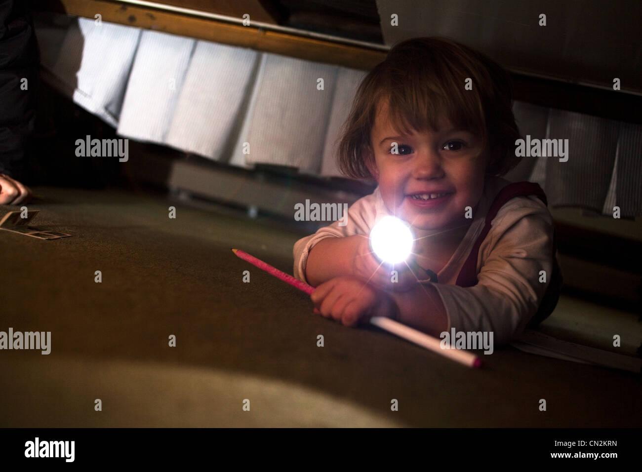 Junge Mädchen spielen mit Fackel unter Bett Stockbild