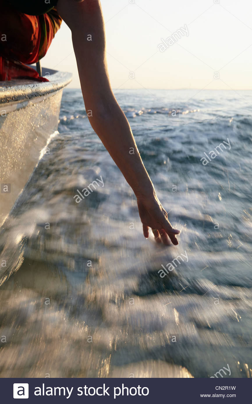 Ältere Frau im Motorboot, hand im Wasser Stockbild