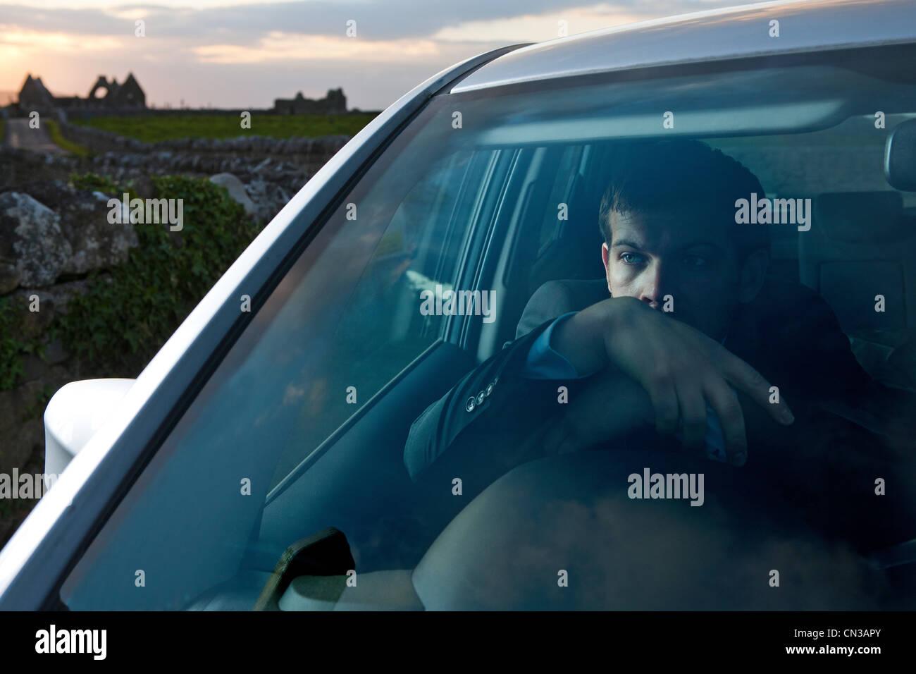 Geschäftsmann, stützte sich auf Lenkrad im Auto Stockbild