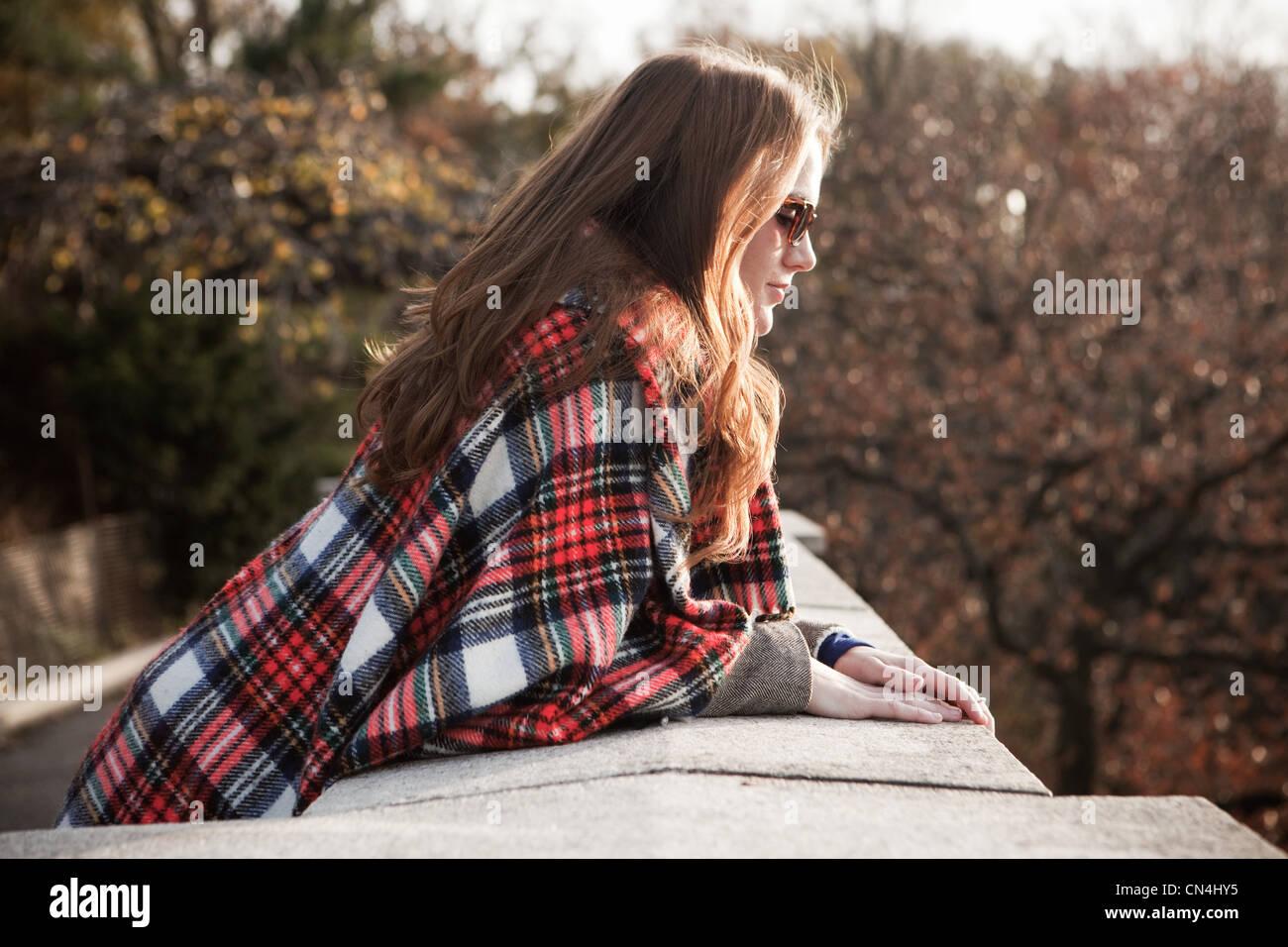 Mädchen mit karierten Decke mit Blick auf Wand Stockbild