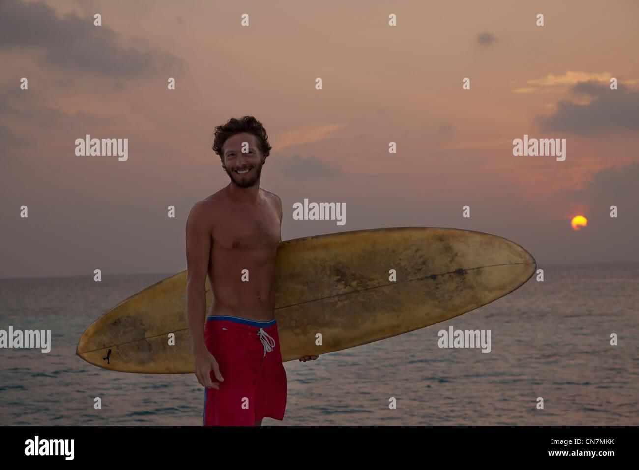Surfer tragen Board am Strand bei Sonnenuntergang Stockbild