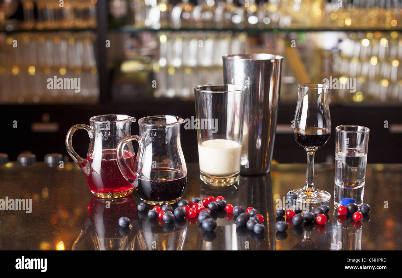 Verschiedene Gläser mit Flüssigkeiten in ihnen neben einem cocktail-Shaker auf einem Zähler Stockbild
