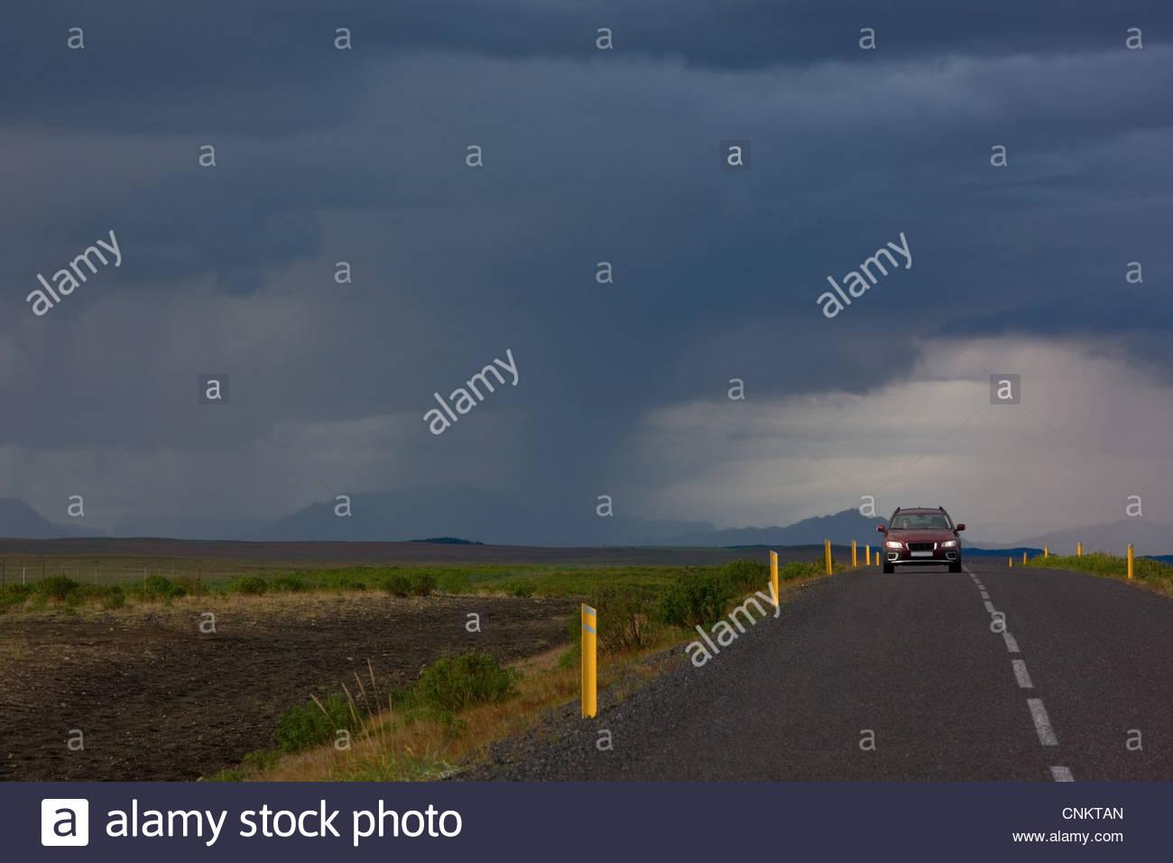 Auto auf der Landstraße unter dramatischen Himmel Stockbild