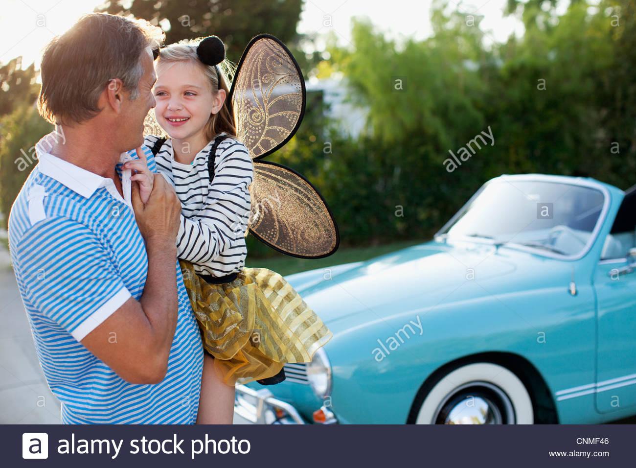 Vater Holding-Tochter in Feenflügel Stockfoto