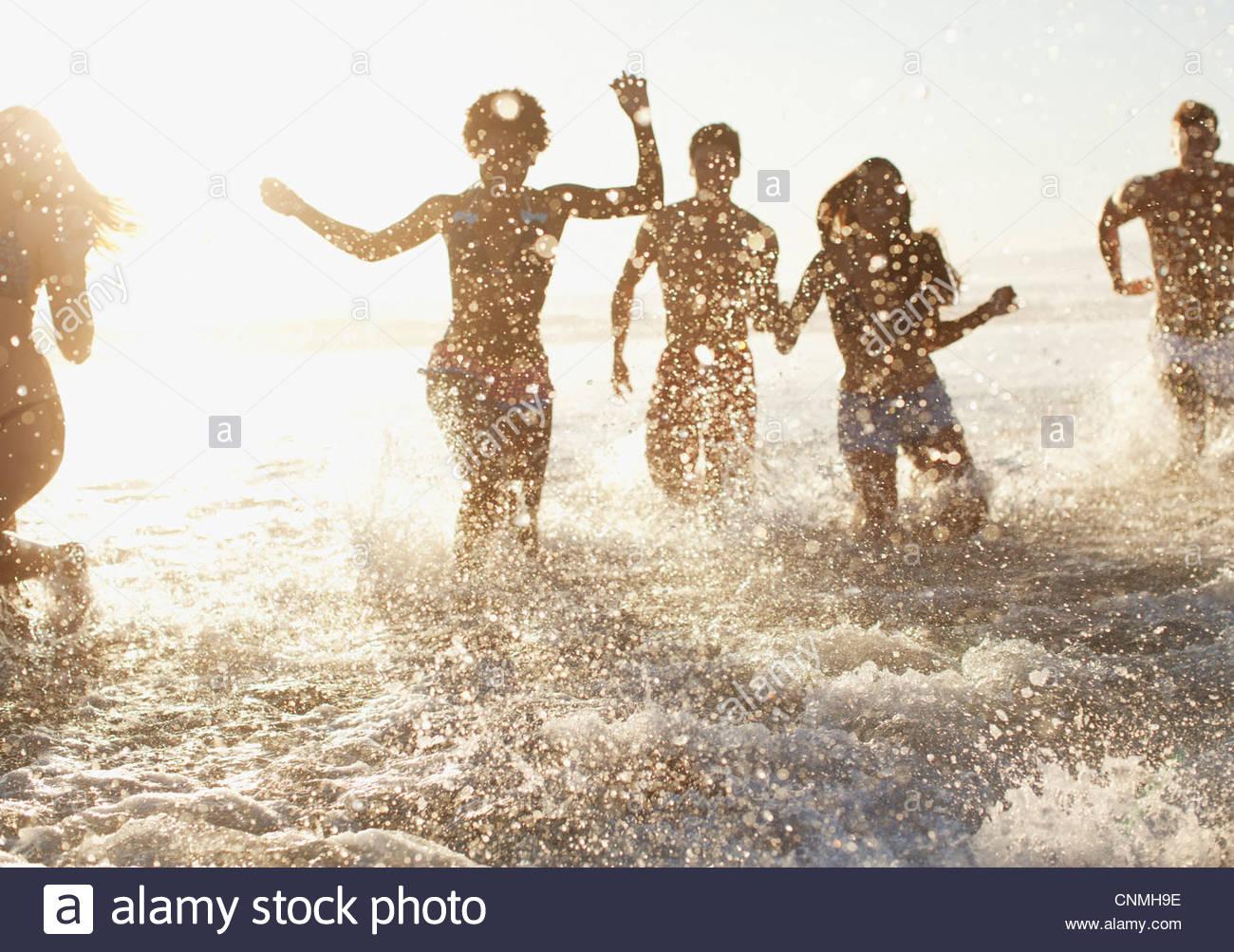 Freunde spielen in Wellen am Strand Stockbild