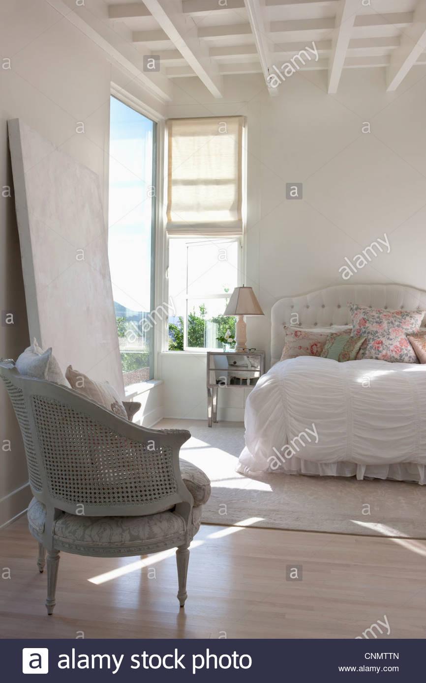 Stuhl und Bett in kunstvollen Schlafzimmer Stockbild