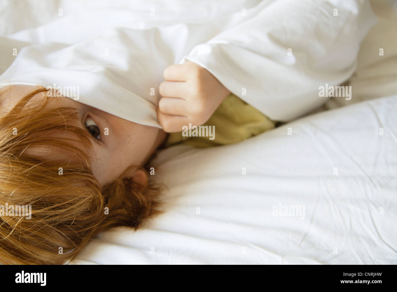 Junge versteckt unter Bettlaken Stockbild
