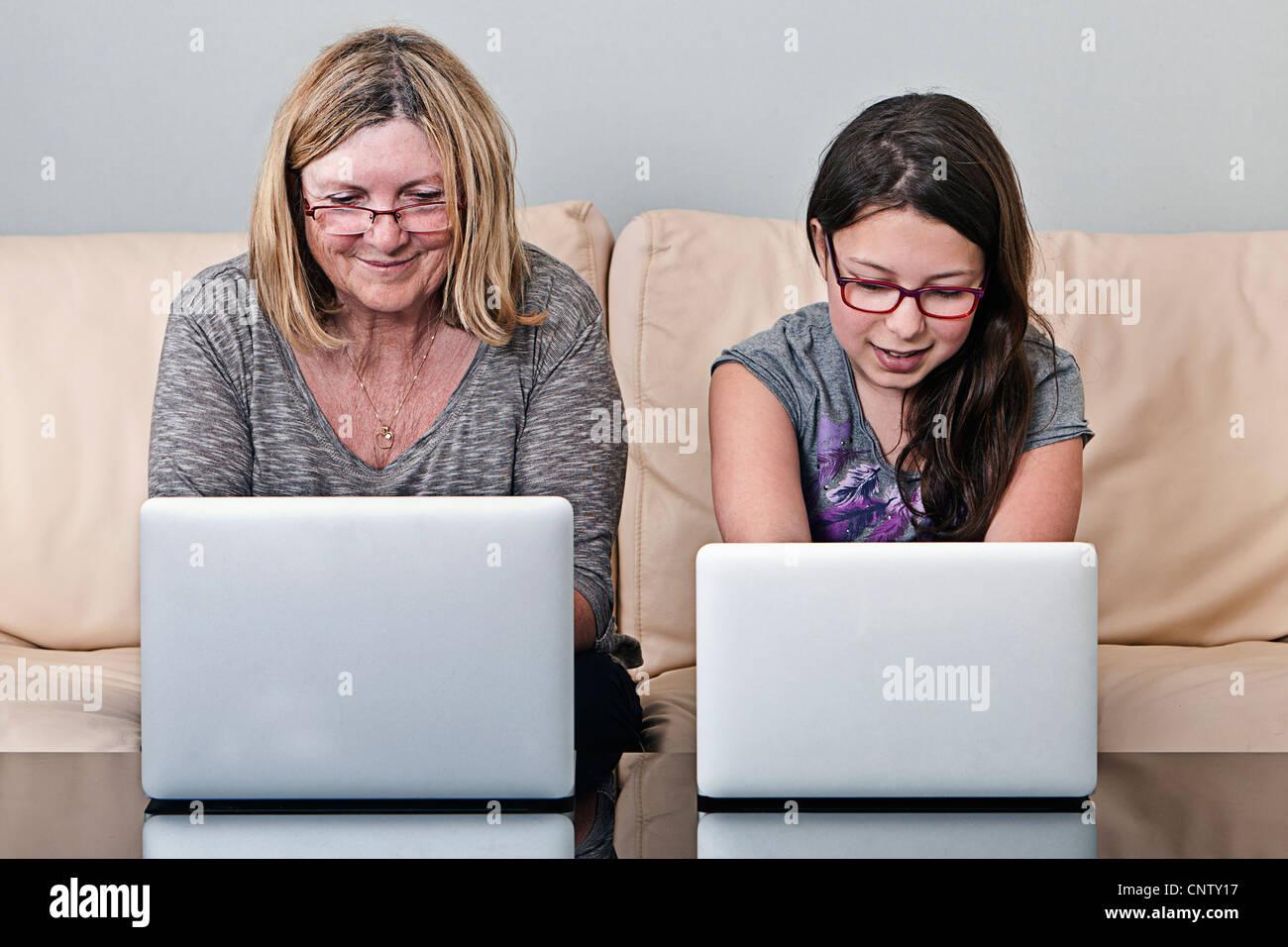 Großmutter und Enkelin mit Laptops Stockbild