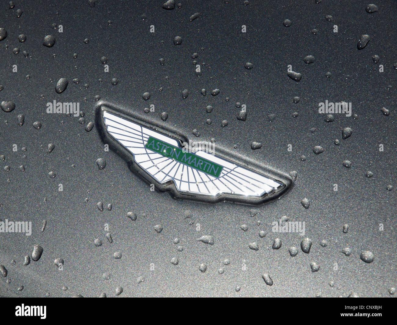 Aston Martin Emblem auf Motorhaube mit ausgefallenen metallic Lackierung mit Regentropfen. Stockbild