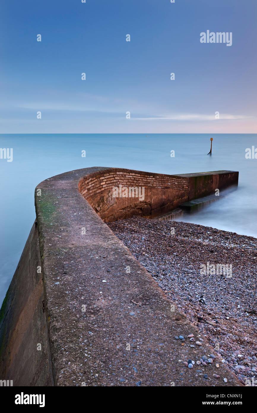 Stein-Anlegestelle am Sidmouth Strand bei Sonnenuntergang, Sidmouth, Devon, England. Winter (Januar) 2012. Stockbild