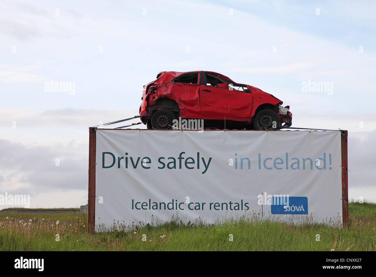 Denkmal an einem Straßenrand mit einem Junk-e-Auto und die Warnung, vorsichtig, Island, Gardur zu fahren Stockbild