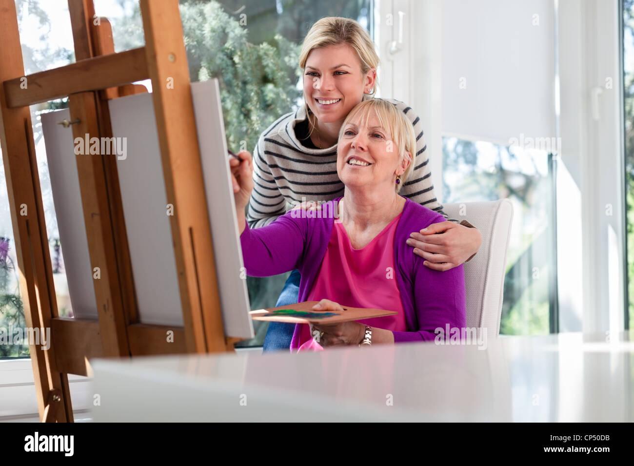 Familienbild mit glückliche Mutter malen für Hobby und Tochter lächelnd und umarmen ihr zu Hause Stockbild