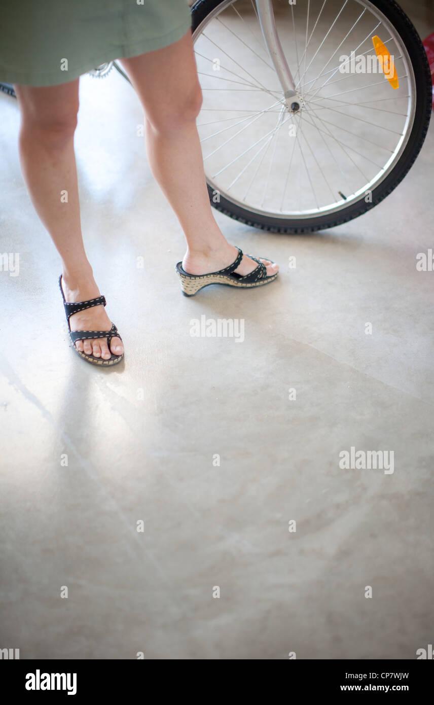 Frau trägt Sandalen stehen neben einem Fahrrad-Reifen. Stockbild