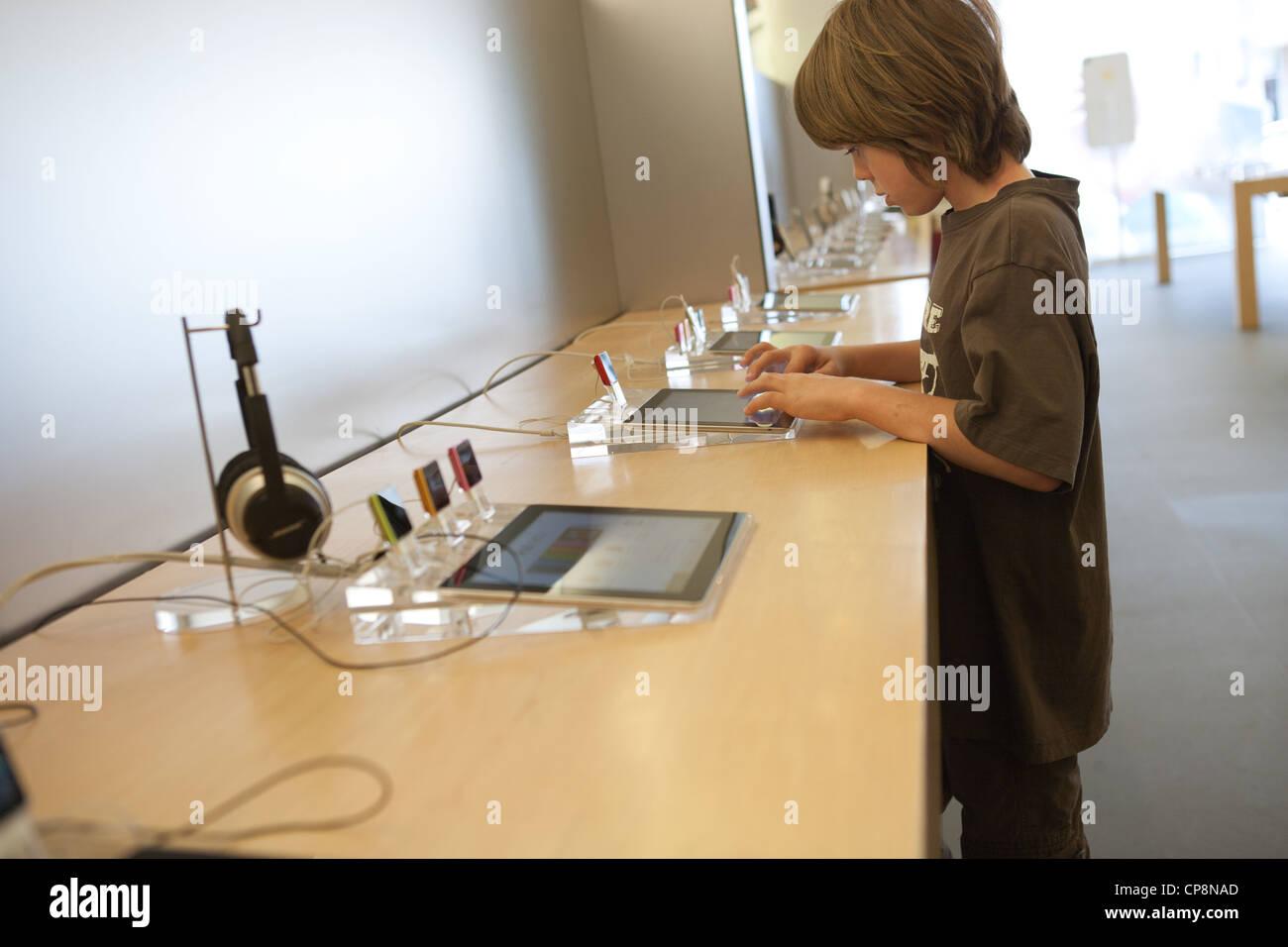 Neun Jahre alten Jungen Experimente mit einem Ipad Tablet in einem Apple Store. Stockbild