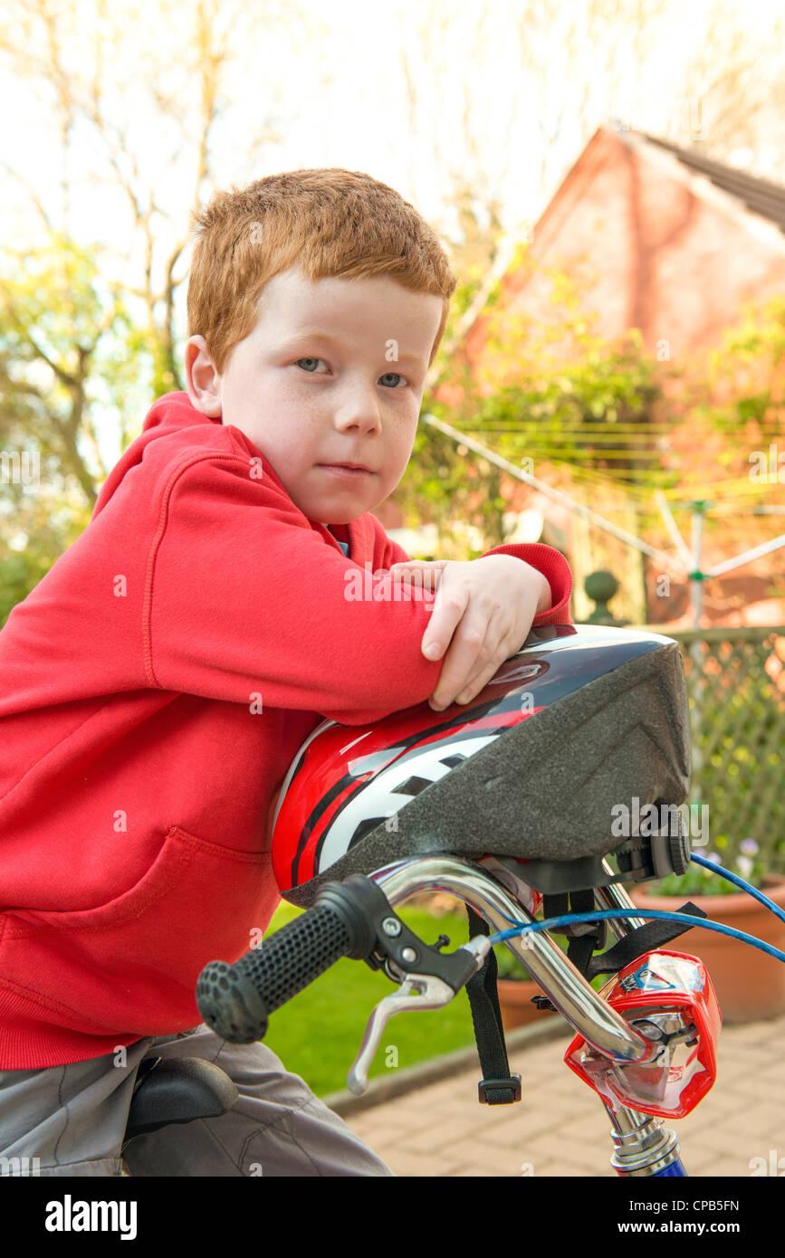 Kleiner Junge auf seinem Fahrrad in seinem Garten, Blick auf Kamera. Stockbild