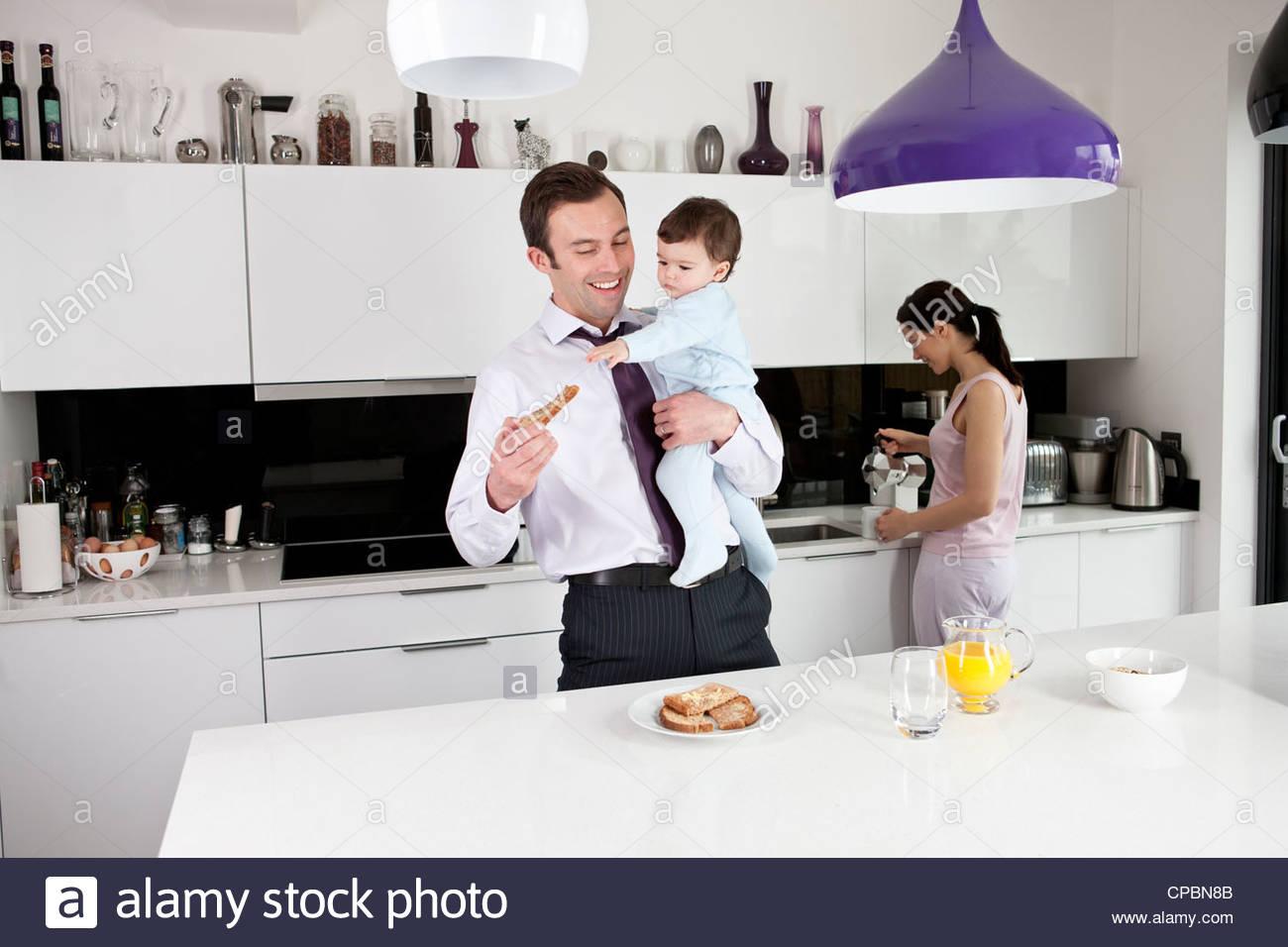 Ein Vater versucht, seine frühstücken während sein kleiner Sohn halten Stockbild