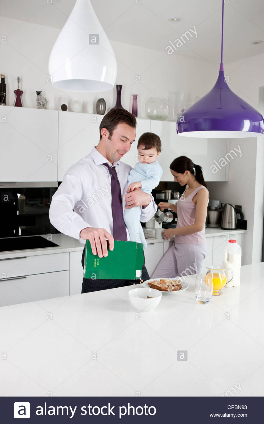 Ein Vater, sein kleiner Sohn halten, während das Frühstück machen Stockbild