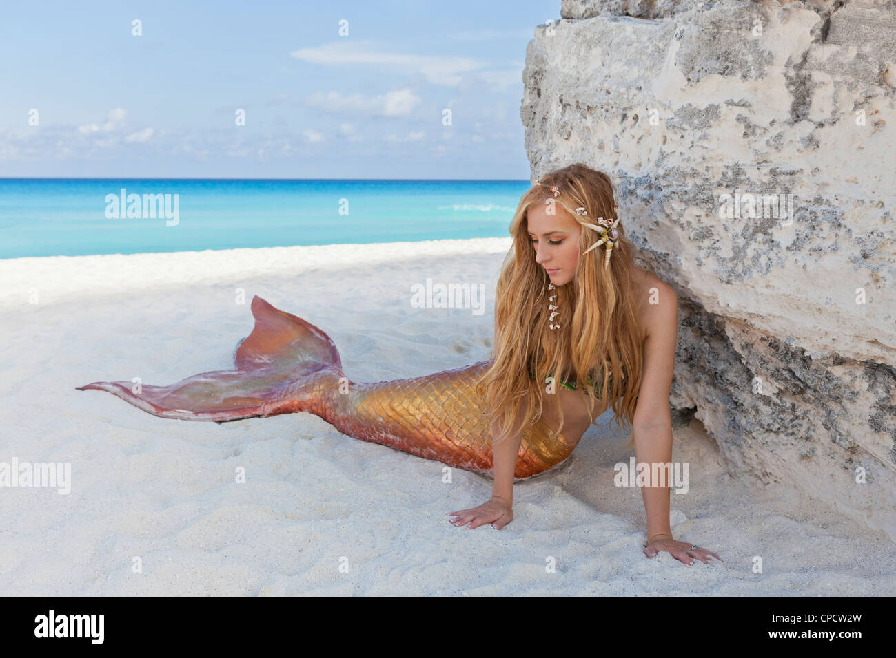 Junge blonde Meerjungfrau am Strand in Cancún, Mexiko Stockbild