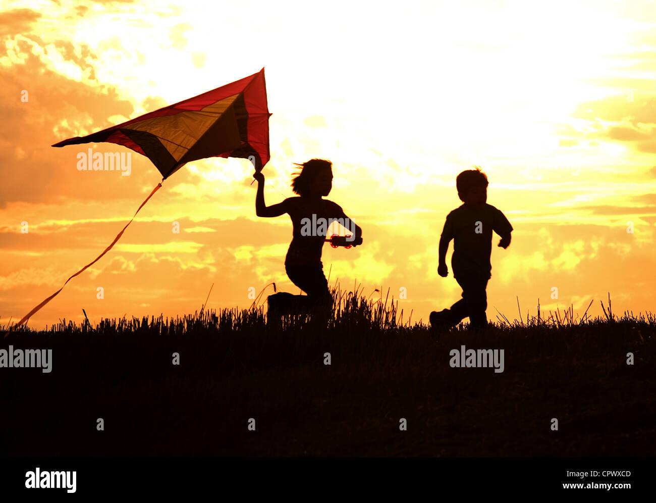 Zwei Kinder Drachen bei Sonnenuntergang rufen Erinnerungen an die Kindheit. Stockbild