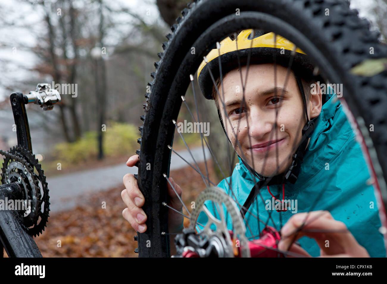 Junger Mann Befestigung Fahrrad-Rad im Wald Stockbild