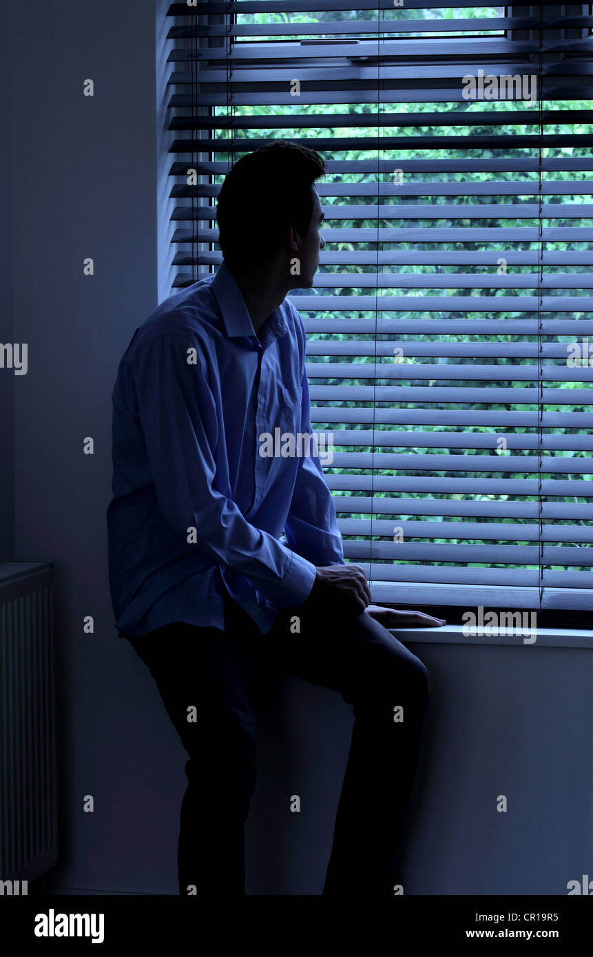 Junger Mann sitzt in einem dunklen Raum mit Blick durch ein Fenster Blind. Stockbild