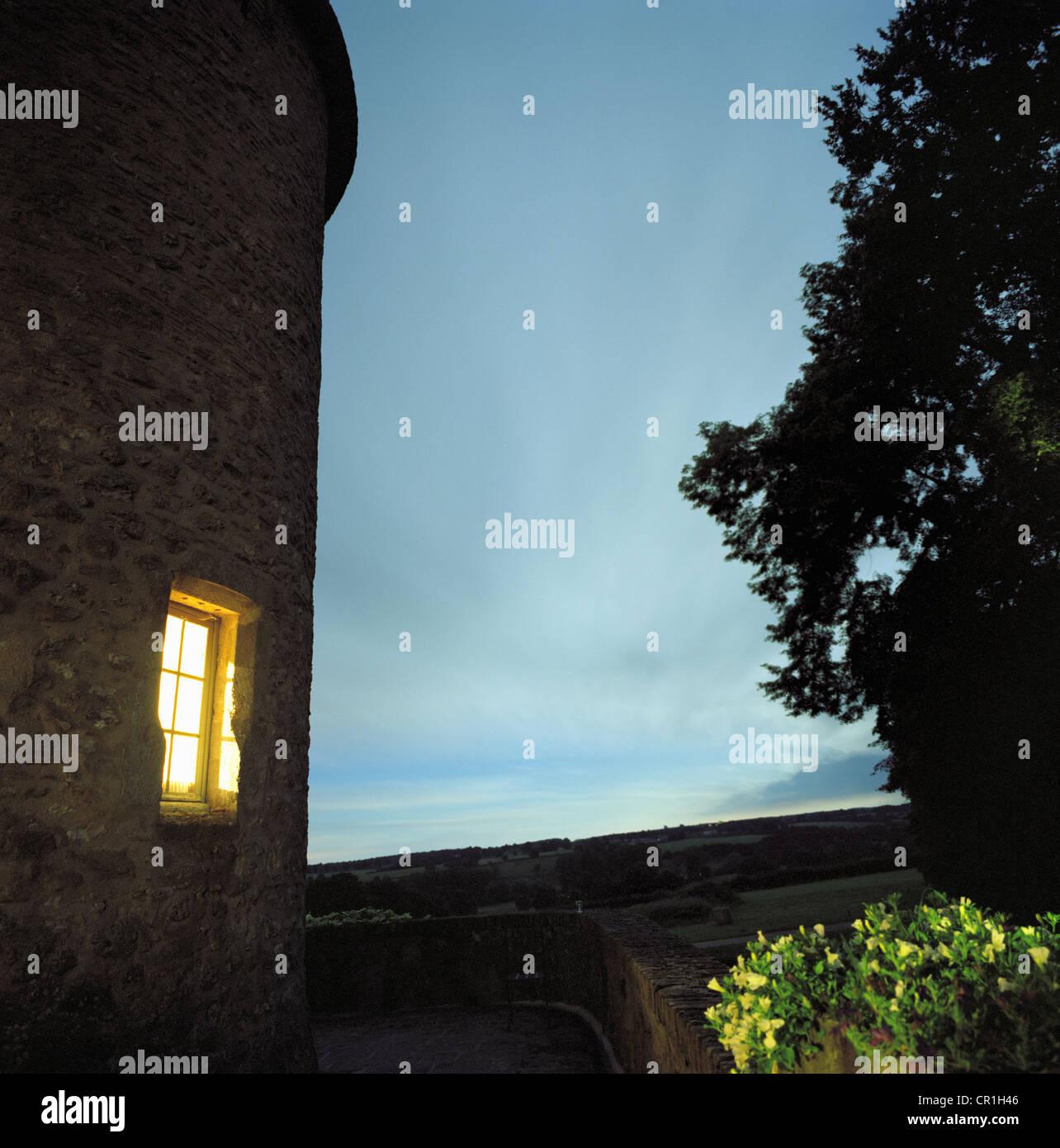 Beleuchtete Fenster von Haus aus Stein Stockbild