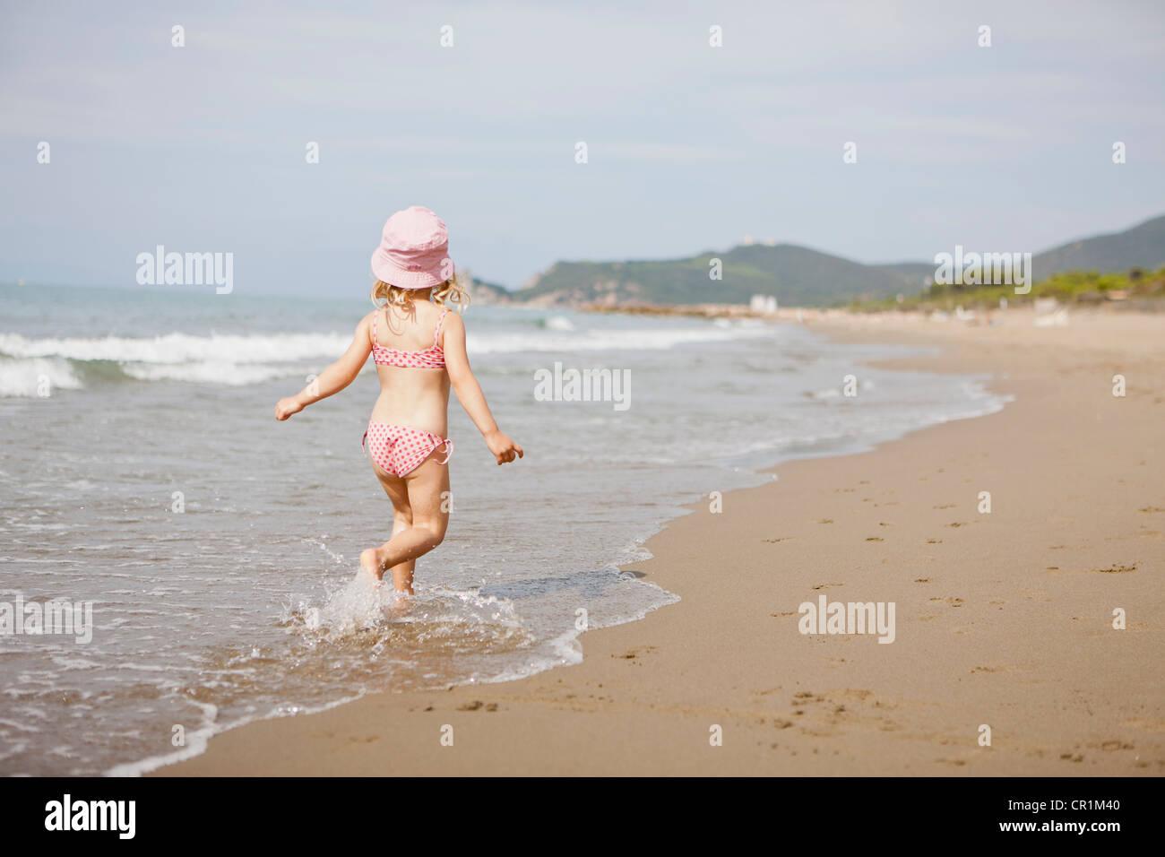 Mädchen in Wellen am Strand zu Fuß Stockbild