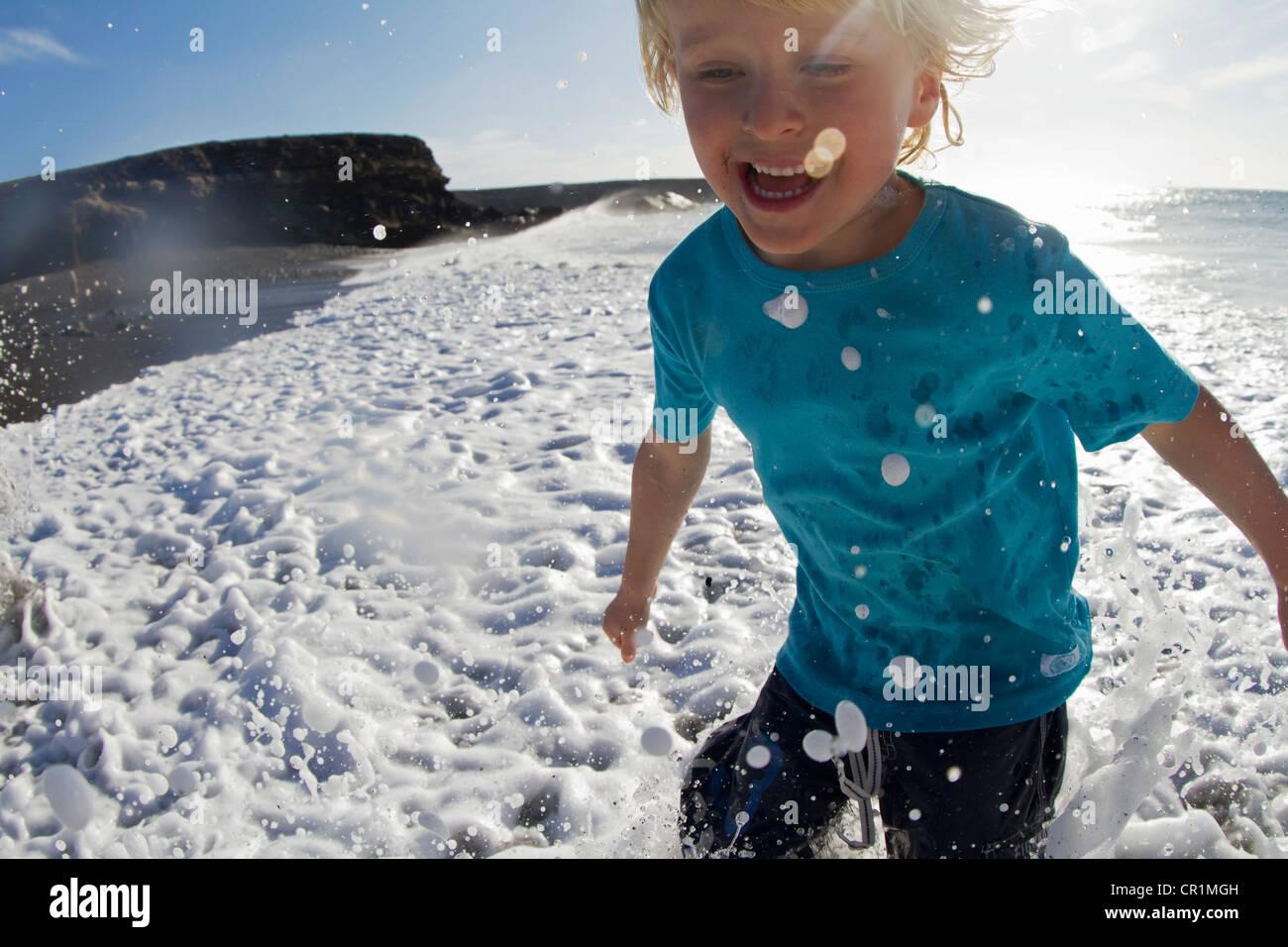 Jungen spielen in Wellen am Strand Stockbild